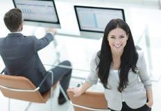 站立在现代工作场所附近的成功的女商人 免版税库存图片