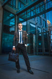 站立在现代办公室附近的年轻英俊的成功的时髦的商人 免版税图库摄影