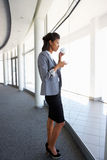 站立在现代办公楼饮用的咖啡走廊的年轻女实业家  免版税库存图片