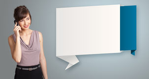 站立在现代origami拷贝空间和maki旁边的俏丽的妇女 免版税库存照片