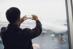 站立在玻璃墙旁边的英俊的人在现代机场终端,拍飞机航空器的照片照片 免版税库存照片