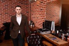 站立在理发店的英俊的年轻美发师画象在扶手椅子,发式专家附近在椅子上把一只手放 免版税库存照片