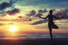 站立在瑜伽姿势的妇女剪影在意想不到的日落期间 免版税库存图片
