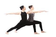 站立在瑜伽战士II姿势的两个信奉瑜伽者女孩 库存照片