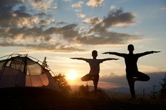 站立在瑜伽的妇女剪影和男孩摆在日落靠近野营在美丽的天空下 免版税库存图片