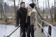 站立在瑞典冬天风景的桥梁的一对美好的斯堪的纳维亚年轻夫妇的照片 免版税库存图片