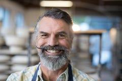 站立在瓦器车间的愉快的男性陶瓷工 库存图片