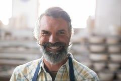 站立在瓦器车间的愉快的男性陶瓷工 免版税库存照片
