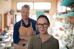 站立在瓦器车间的男性和女性陶瓷工 库存照片