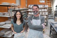 站立在瓦器车间的男性和女性陶瓷工 库存图片