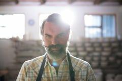 站立在瓦器车间的男性陶瓷工 免版税库存图片