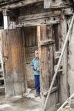 站立在甘肃的门的孩子 免版税库存图片