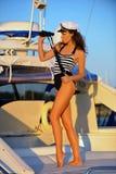 站立在甲板和拿着双筒望远镜的黑白泳装的妇女 免版税库存照片