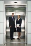 站立在电梯的企业同事 库存照片