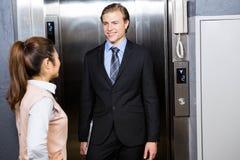 站立在电梯的商人和女实业家 免版税库存照片