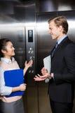 站立在电梯的商人和女实业家 库存图片