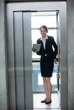 站立在电梯的女实业家拿着一种数字式片剂 库存照片