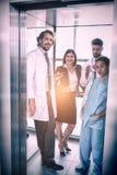 站立在电梯的医生和女实业家 图库摄影