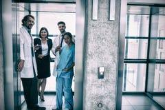 站立在电梯的医生和女实业家 免版税图库摄影
