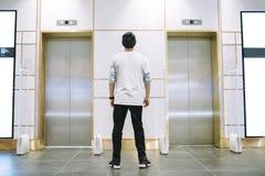站立在电梯附近的帽子的人 免版税库存图片