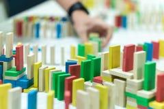 站立在白色书桌上的复杂的行的五颜六色的多米诺 库存图片