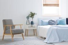 站立在白色卧室内部wi的镶边地毯的扶手椅子 库存图片