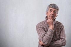 站立在白色墙壁附近的英俊的老人画象作梦关于看的某事在旁边握他的手在他的下巴下 库存照片