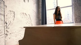 站立在白色大平台钢琴后的可爱的女孩 股票录像