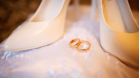 站立在白色枕头的婚礼鞋子和圆环 免版税库存图片