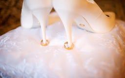 站立在白色枕头的婚礼鞋子和圆环 免版税库存照片