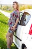站立在白色汽车附近的愉快的孕妇 图库摄影