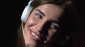 站立在白色耳机和微笑的愉快的妇女音乐爱好者 股票视频