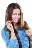 站立在白色背景和拿着一支红色唇膏的一件蓝色毛线衣的美丽的女孩 微笑 库存图片