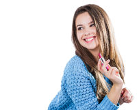 站立在白色背景和拿着一支红色唇膏的一件蓝色毛线衣的美丽的女孩 微笑 免版税库存图片