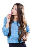站立在白色背景和拿着一支红色唇膏的一件蓝色毛线衣的美丽的女孩 被洗染的嘴唇 免版税库存图片