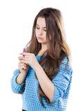 站立在白色背景和拿着一支红色唇膏的一件蓝色毛线衣的美丽的女孩 免版税图库摄影