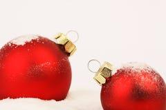 站立在白色背景的雪的两个多雪的红色圣诞节暗淡球 免版税库存照片