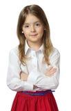站立在白色衬衣&红色裙子的逗人喜爱的儿童女孩被隔绝  免版税库存照片