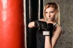 站立在白色,黑和红颜色装饰的健身房的沙袋旁边的金发运动女孩 免版税库存图片