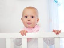 站立在白色轻便小床的一个逗人喜爱的婴孩的画象 免版税库存图片