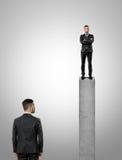 站立在看另一个商人的一个混凝土桩的峰顶的商人 图库摄影