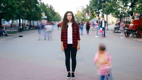 站立在看照相机的拥挤的街上的市中心的可爱的少妇定期流逝穿便衣 影视素材