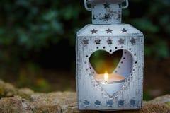 站立在石头的葡萄酒金属心脏形状蜡烛台升灼烧的火焰在庭院里 华伦泰母亲` s天 免版税库存图片