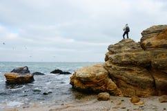 站立在石灰石岩石,傲德萨,黑海上面的旅行家  库存照片