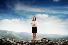 站立在石头的女实业家 免版税图库摄影
