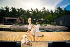 站立在码头的人在膝盖提出结婚提议 库存图片
