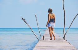 站立在码头的牛仔裤的热的女孩 库存照片