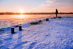 站立在码头的渔夫在黎明天空背景与太阳光芒和反映在海水 免版税库存照片