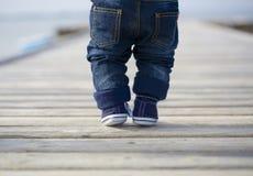 站立在码头的婴孩腿 免版税图库摄影