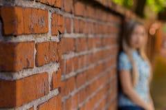 站立在砖墙和等待附近的Blured女孩 背景blured 库存图片